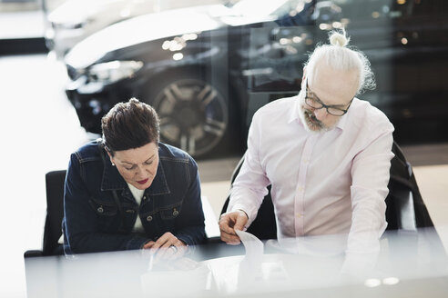 Senior man and woman reading documents while sitting at car showroom - MASF03409