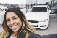 Portrait of smiling young woman standing against car - MASF03415