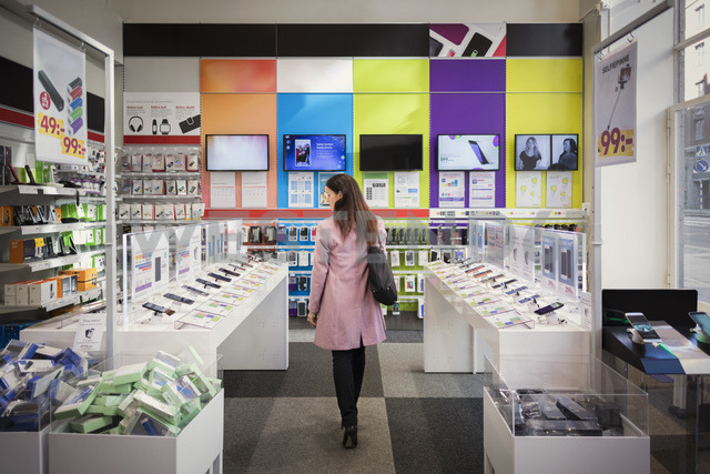 Rear view of female customer viewing smart phones in store - MASF03421