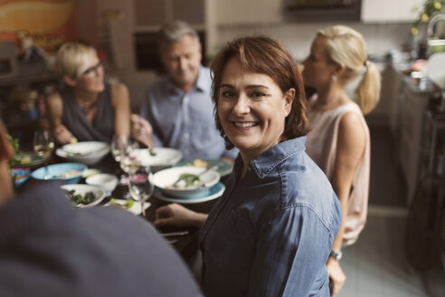 Portrait of happy mature woman sitting with friends at table - MASF03427