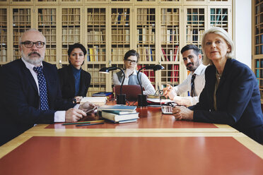 Portrait of lawyers sitting in board room against bookshelf - MASF03439