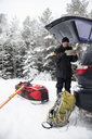 Male hiker reading map while standing by car with open trunk during winter - MASF03442