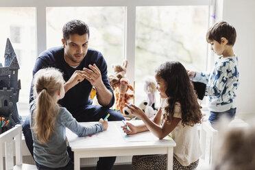Male teacher with students in preschool - MASF03445