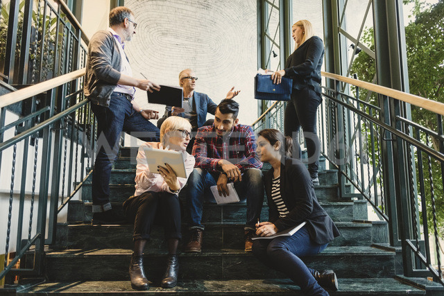 Multi-ethnic business people discussing on stairway in creative office - MASF03466