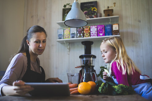Mother showing digital tablet to daughter on table - MASF03493