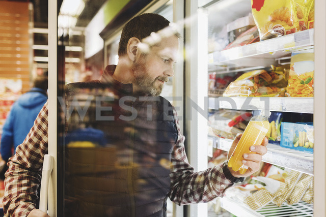 Male customer reading drink label seen through glass door at refrigerated section - MASF03508