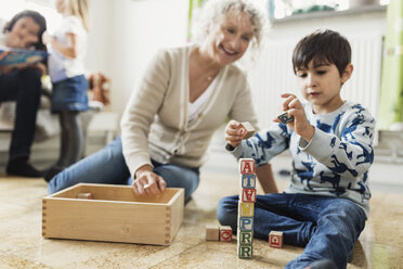 Happy teacher looking at boy stacking blocks at day care center - MASF03511
