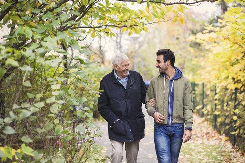 Happy senior man with caretaker walking in park - MASF03520
