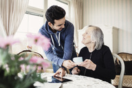 Happy caretaker serving coffee to senior woman in nursing home - MASF03523