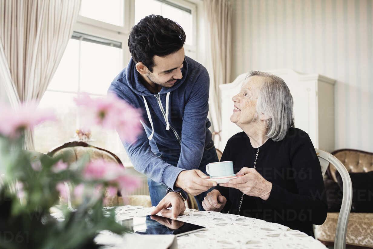 Happy caretaker serving coffee to senior woman in nursing home - MASF03523 - Maskot ./Westend61