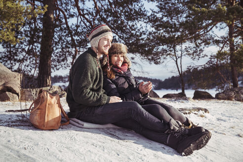 Happy couple enjoying coffee while relaxing on snow covered field - MASF03526