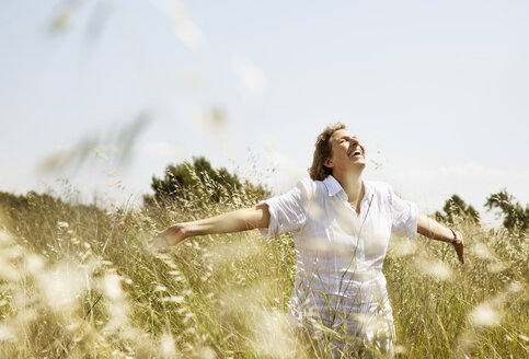 Happy mature woman smiling while walking with arms raised in grass field - MASF03535