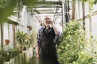 Happy gardener talking on mobile phone while standing in greenhouse - MASF03556