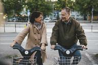 Happy senior couple taking rental bikes at parking lot - MASF03559