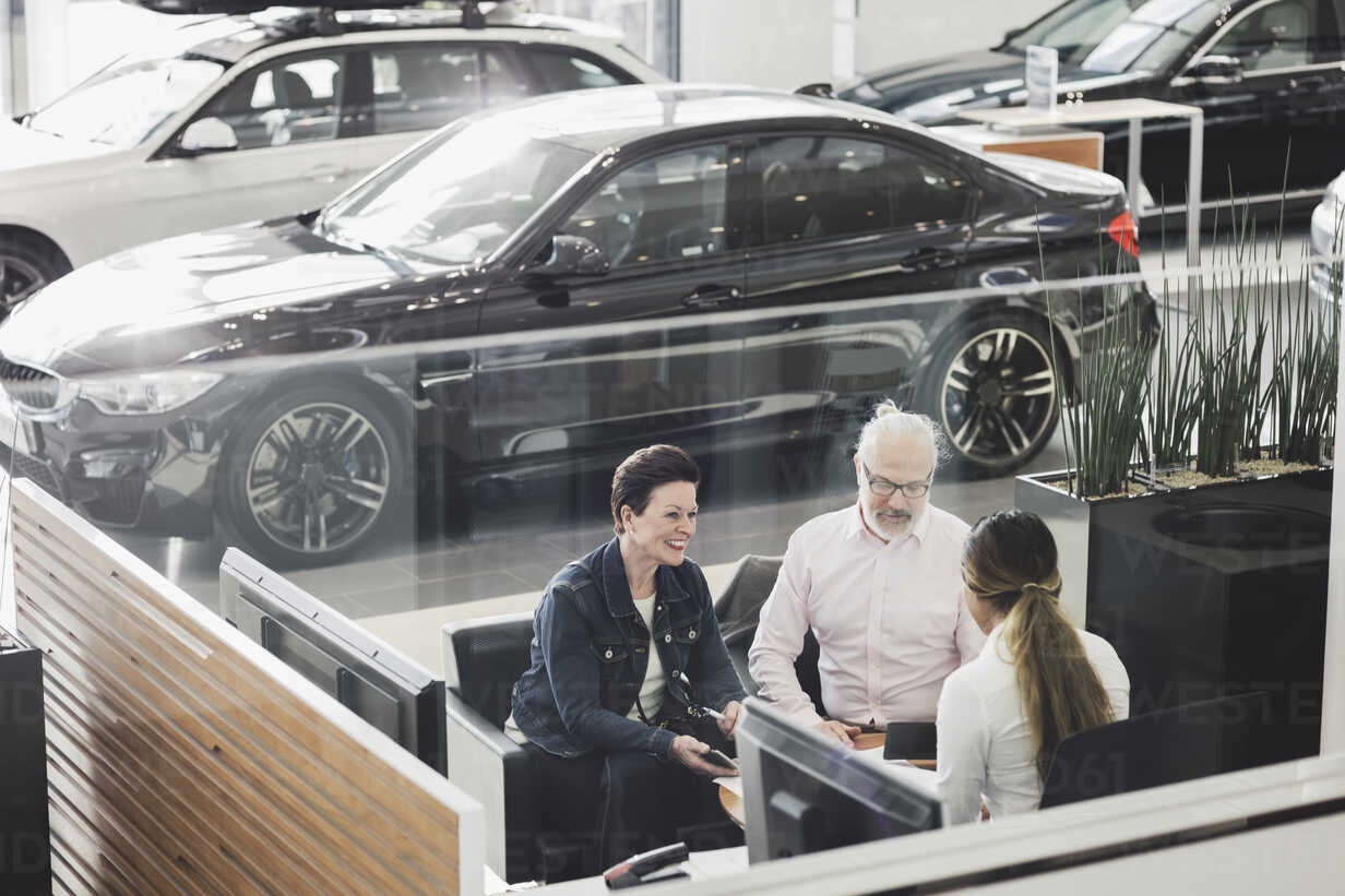 High angle view of saleswoman discussing with customers at car showroom - MASF03574 - Maskot ./Westend61