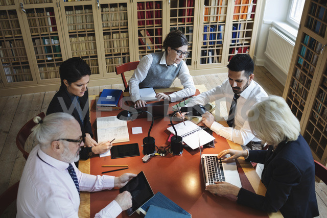 High angle view of professionals working at table in law library - MASF03592