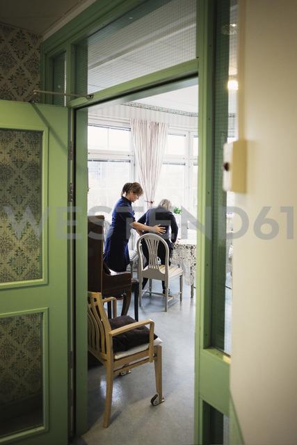 Female caretaker helping senior woman to sit on chair at nursing home - MASF03604 - Maskot ./Westend61