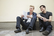 Full length of young male friends sitting down on floor looking away and smiling - MASF03613