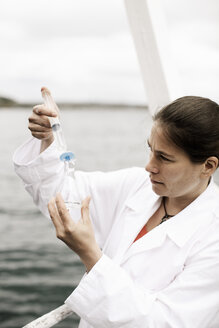 Female scientist injecting water in flask on boat in sea - MASF03664