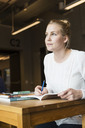 Young woman with book and pen looking away in university classroom - MASF03670