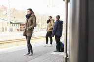 Young woman with friends waiting for train at station - MASF03673