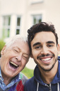 Close-up portrait of caretaker with happy senior man outside nursing home - MASF03685