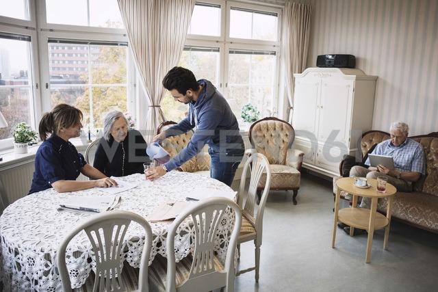 Caretaker pouring drink for senior woman in nursing home - MASF03688 - Maskot ./Westend61