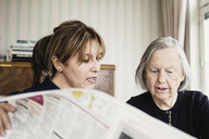 Caretaker with senior woman reading newspaper at nursing home - MASF03691