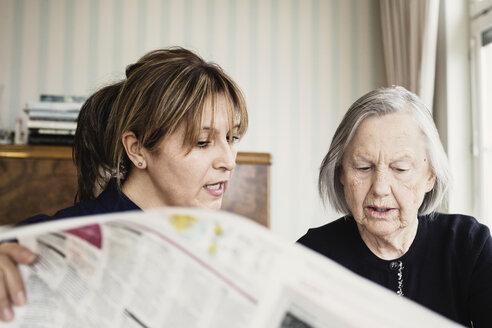 Caretaker with senior woman reading newspaper at nursing home - MASF03691