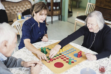 Caretaker playing Ludo with seniors at nursing home - MASF03694