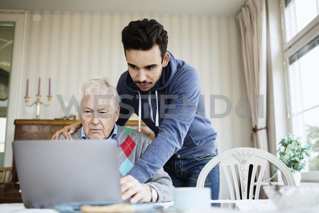 Caretaker assisting senior male in using laptop at nursing home - MASF03697