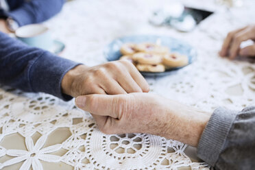 Cropped image of caretaker consoling man at dining table - MASF03700