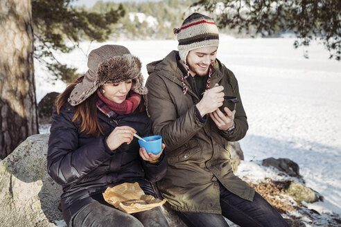 Couple having food while sitting on rock at field during winter - MASF03703