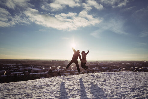 Couple jumping on snow covered mountains against sky - MASF03706