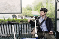 Thoughtful businessman holding bicycle while sitting at bus stop - CAVF38038