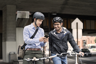 Multi-ethnic male commuters using smart phone on city street - CAVF38044