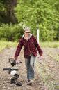 Female farmer carrying seedling trays while walking on farm - CAVF38080