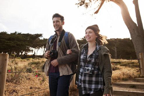 Happy hiking couple walking arm in arm on field - CAVF38107