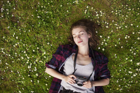 Overhead view of woman holding camera while lying on grass at park - CAVF38116