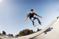 Low angle view of man performing stunt in skateboard park against clear blue sky - CAVF38182