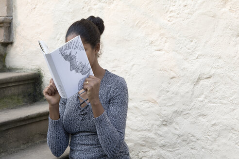 Woman covering face with book, reading poetry in front of wall - PSTF00099