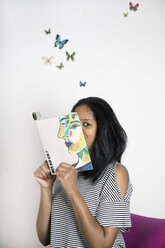 Woman covering face with book, reading poetry with butterflies - PSTF00102