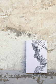 Book with female face on the cover leaning against weathered wall - PSTF00105