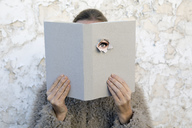 Woman covering face with book, reading poetry, eye looking through cover - PSTF00108