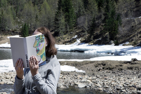 Woman covering face with book, reading poetry in the mountains - PSTF00111