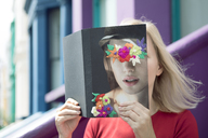 Woman covering face with book, reading poetry in the city - PSTF00114