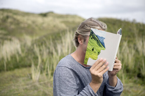 Man reading story book in the dunes, covering his face - PSTF00117