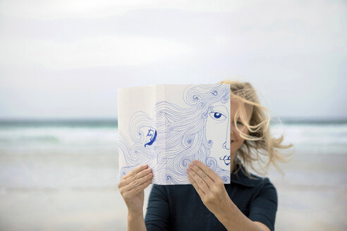 Woman covering face with book, reading poetry on beach - PSTF00120