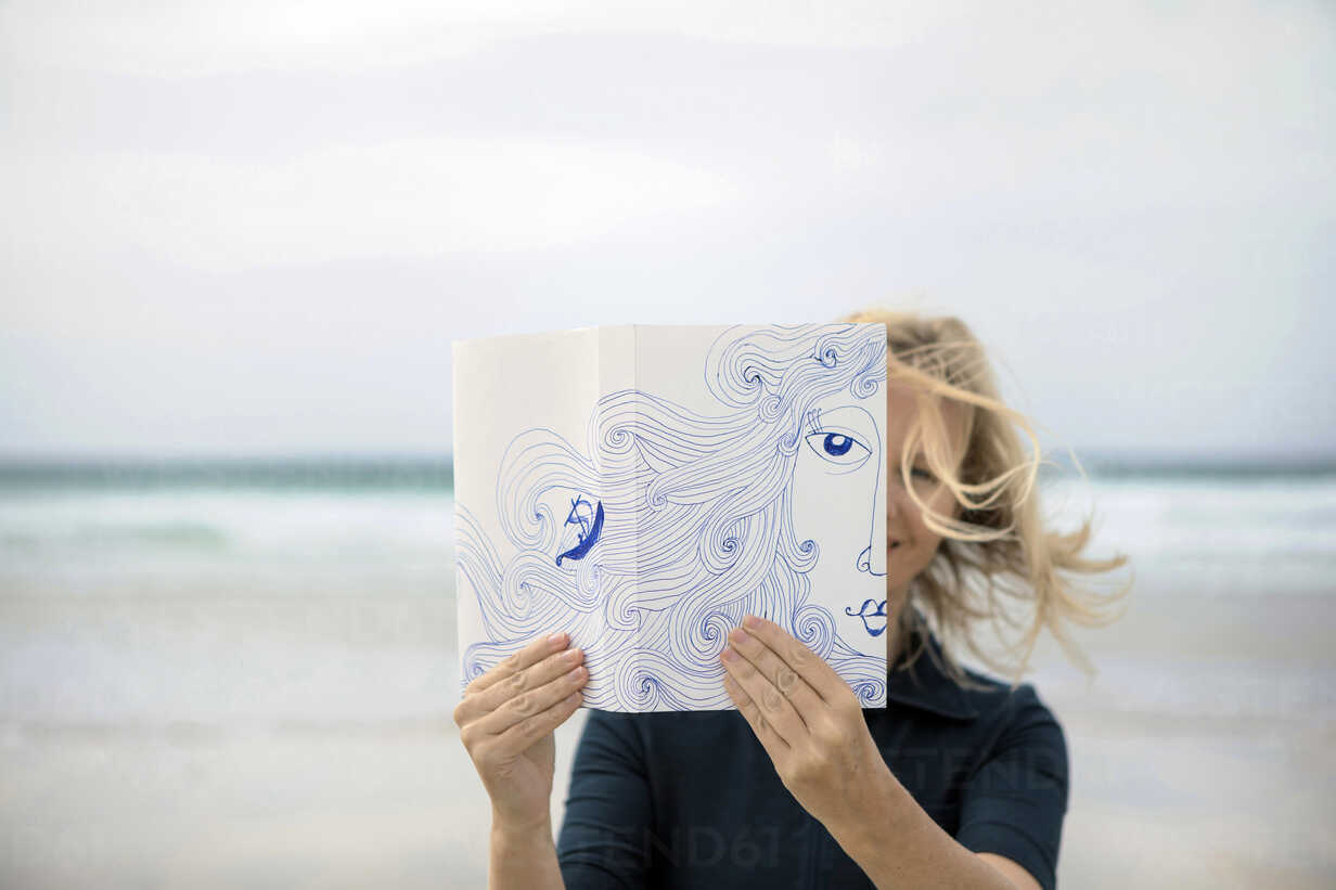 Woman covering face with book, reading poetry on beach - PSTF00120 - Petra Stockhausen/Westend61