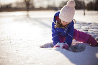 Girl playing with snow on sunny day - CAVF38288